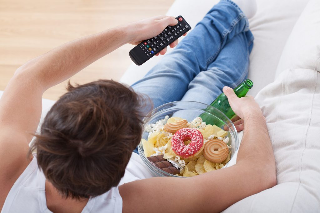 Man watching TV with plate of junk food